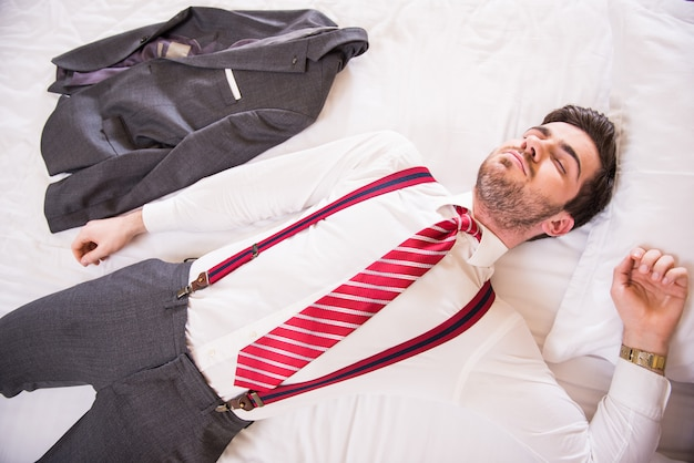 Dressed man lay on bed after hard road.
