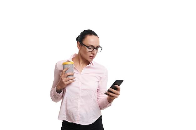 白い背景で隔離の携帯電話でメッセージをテキストメッセージでホットコーヒーまたは紅茶と紙コップを保持しているドレッシングビジネスカジュアルな服装。