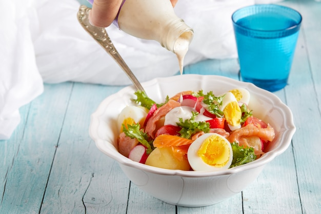 Dressing salad of boiled potatoes, eggs, smoked salmon, cherry tomatoes and lettuce.