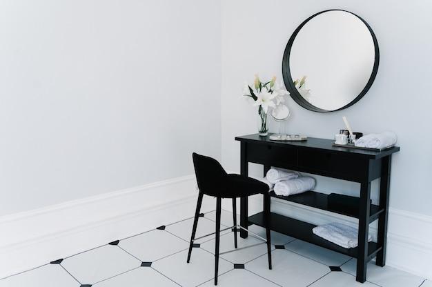 Туалетный столик в ванной с зеркалом и полотенцем
