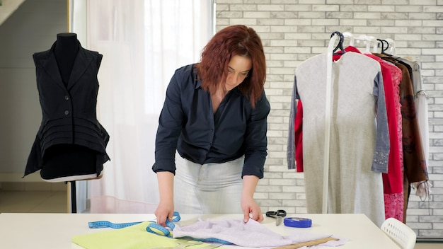 Портниха за работой в своей мастерской швейного ателье. портной измеряет ткань с лентой на столе, чтобы сделать выкройку для будущей одежды на рабочем месте. бизнес по индивидуальному пошиву.
