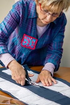 彼女のワークショップで衣服を作るために布を切る洋裁