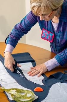 Портниха разрезает ткань, чтобы сшить одежду в своей мастерской