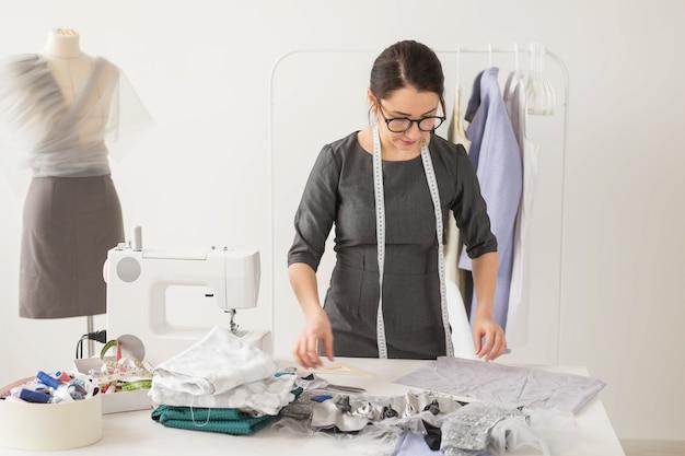양장점, 패션 디자이너 및 재단사 개념-옷 선반 근처 직장에서 아름다운 젊은 스타일리스트.
