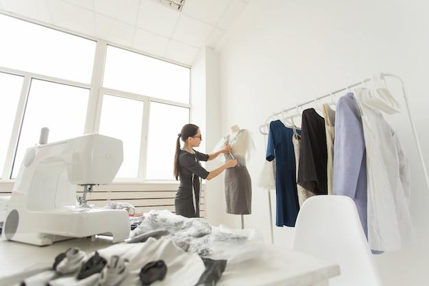 양장점, 패션 디자이너 및 재단사 개념-디자이너는 마네킹에 의상을 장식합니다.
