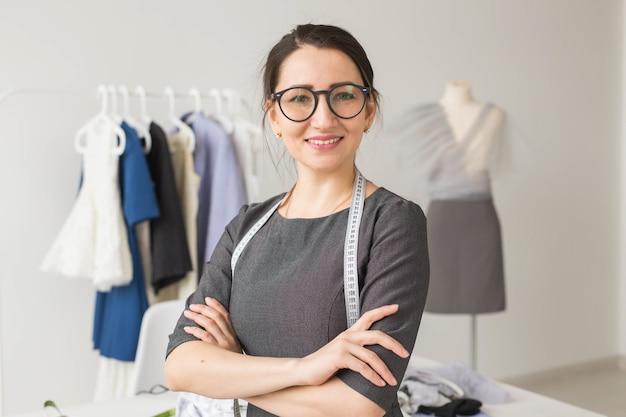 洋裁、ファッションデザイナー、仕立て屋のコンセプト-洋服ラックの上の若い洋裁の女性
