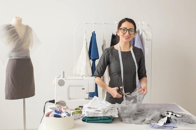洋裁、ファッションデザイナー、仕立て屋のコンセプト-若い女性デザイナーが美しい軽い生地をカット
