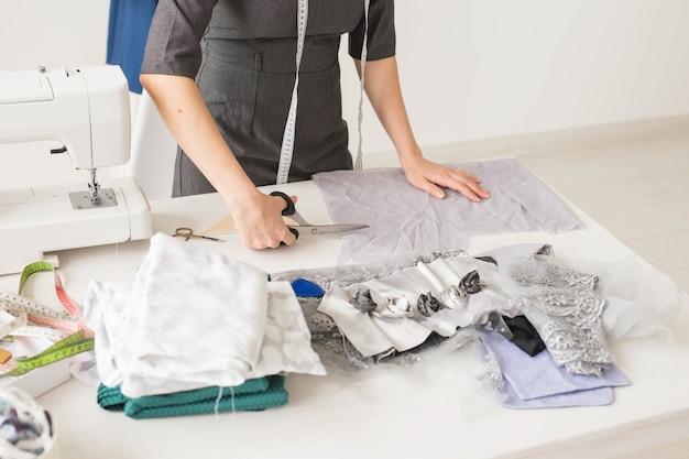 Портниха, модельер и портной концепция - молодая женщина-дизайнер, процесс создания платья