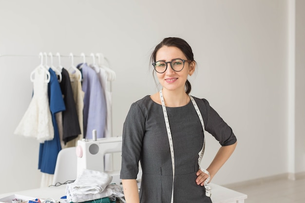洋裁、ファッションデザイナー、仕立て屋、人々のコンセプト-美しいファッション女性デザイナーが立っています