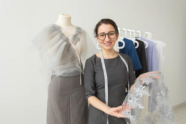 양장점, 패션 디자이너, 재단사 및 사람들 개념-그녀의 젊은 여성 패션 디자이너