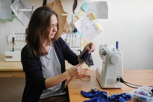 Портниха делает шаблон и работает на швейной машинке.