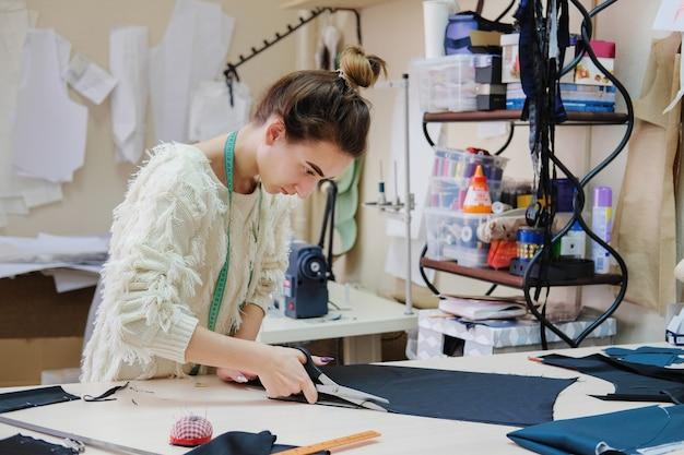 Портниха изготавливает шаблон и работает на швейной фабрике.