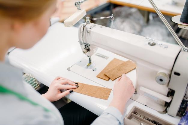 Портниха сшивает ткань на швейной машине