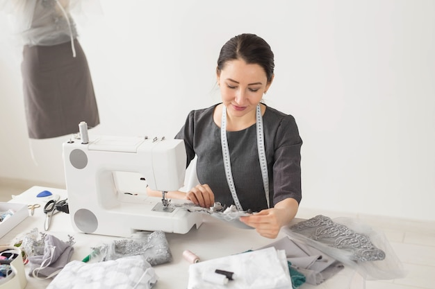 Dressmaker, tailor and creative concept - portrait of fashion designer with sewing machine over white surface