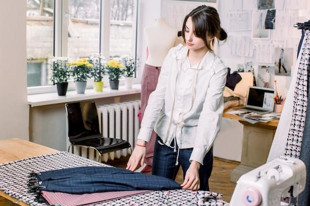 Портниха, портной, мода и концепция шоу-рума - портрет талантливой женской портнихи, работающей с текстилем для шитья одежды
