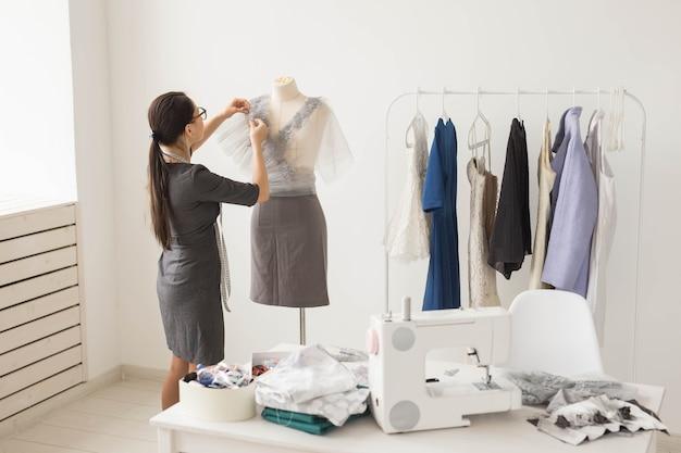 양장점, 재단사, 패션 및 쇼룸 개념-재봉 옷을 위해 섬유로 작업하는 재능있는 여성 양장점의 초상화
