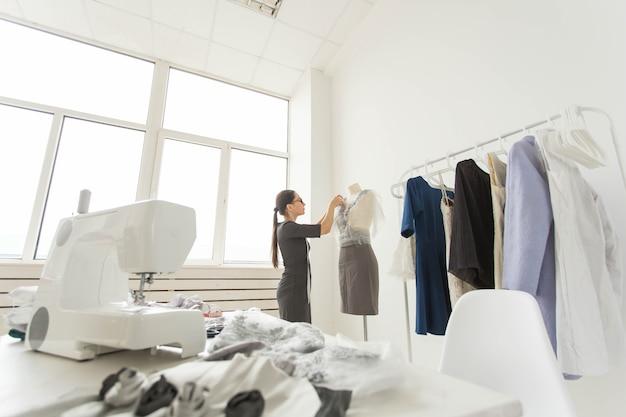 洋裁、仕立て屋、ファッション、ショールームのコンセプト-服を縫うためにテキスタイルを扱う才能のある女性の洋裁の肖像画