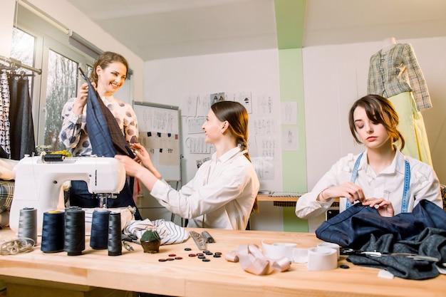 Концепция портнихи, портного, моды и выставочного зала - портрет трех молодых талантливых женщин-портних, создающих новые модные стили брюк и одежды.