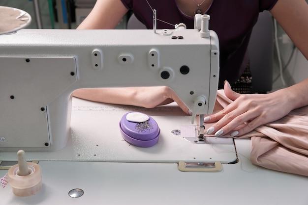 Dressmaker using sewing machine in tailor studio