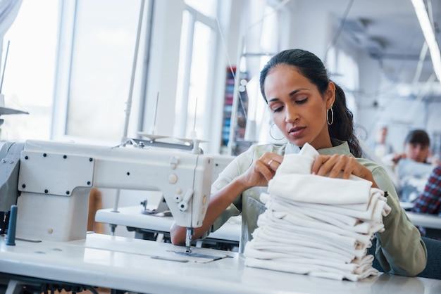 Женщина-портниха шьет одежду на швейной машине на фабрике.