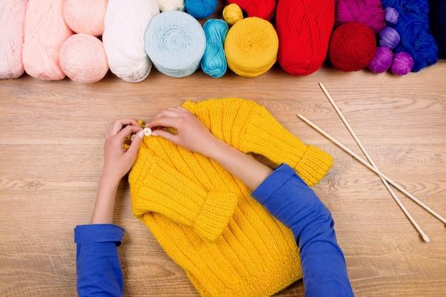 仕立て屋の職場。黄色の赤ちゃんのブーツと糸の黄色のボールで黄色のセーターを作る女性女性の手