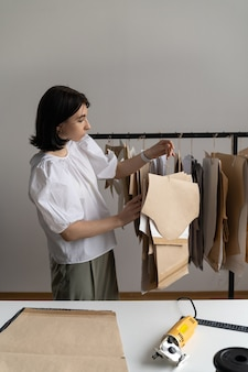 Процесс пошива одежды модельер в модной одежде держит вешалки с бумажными выкройками в студии