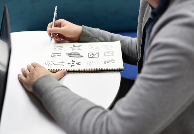 Рука, держащая ноутбук с логотипом бренда drew creative design ideas