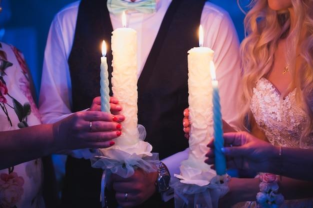 レストランでの結婚式中にキャンドルを保持している新郎新婦