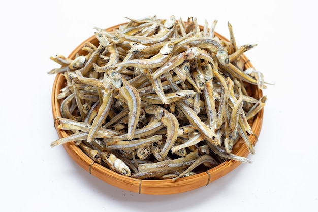 Dried anchovy in bamboo basket on white background