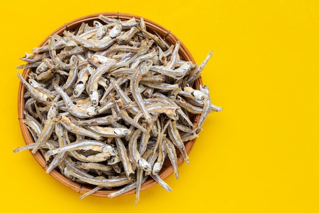 Dried anchovy in bamboo basket on yellow background.