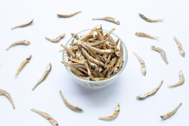 Dried anchovy in glass bowl on white background.