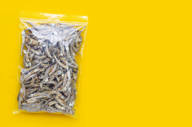 Dried anchovy plastic bag on yellow background.