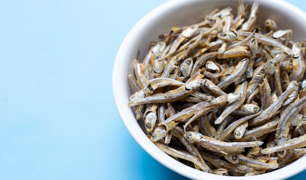 Dried anchovy in white bowl on blue background.