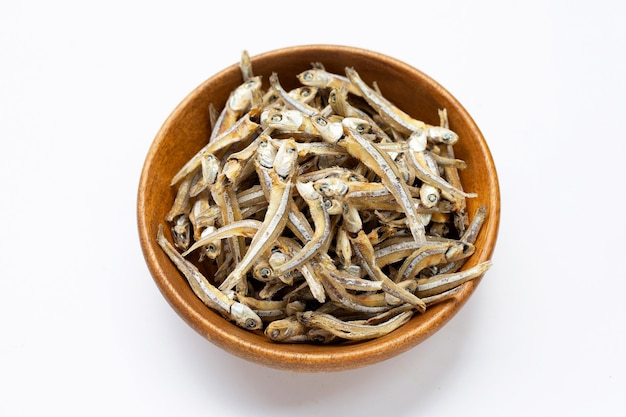 Dried anchovy in wooden bowl on white background