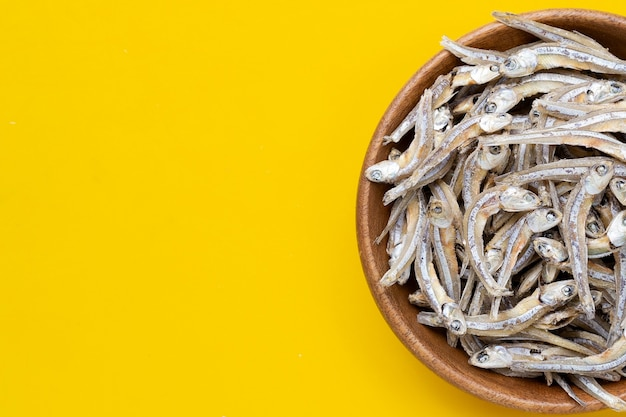 Dried anchovy in wooden bowl on yellow background.