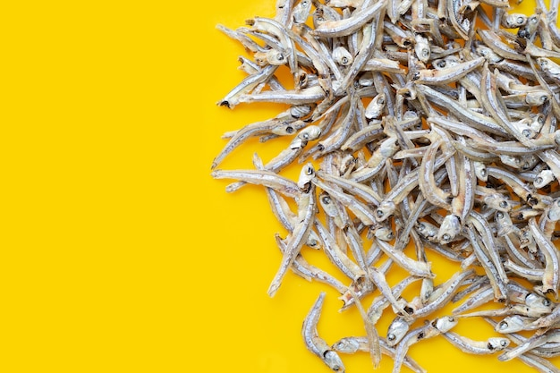 Dried anchovy on yellow background.