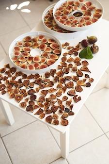 Сушеный и свежий инжир раскладывают на столе в процессе сушки.