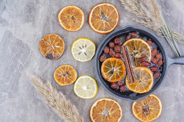 石の表面にシナモンを添えた、乾燥した新鮮なレモンスライス。