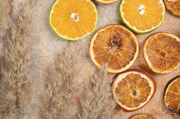 Сушеные и свежие дольки апельсина на мраморном фоне.