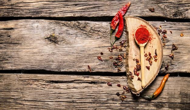 오크에 건조 하 고 지상 붉은 칠리 페 퍼는 나무 테이블에 서있다. 평면도