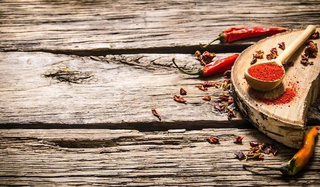 오크에 건조 하 고 지상 붉은 칠리 페 퍼는 나무 테이블에 서있다.