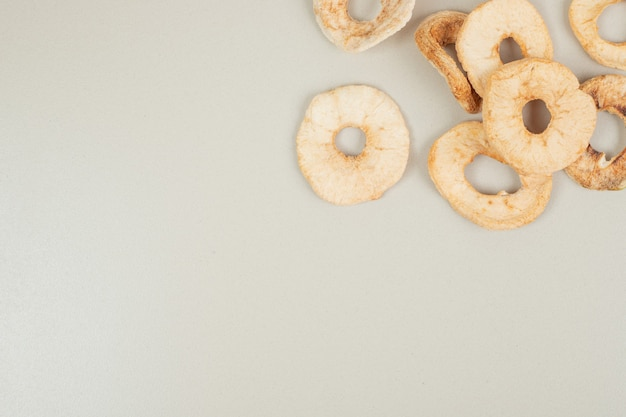 Dried apple chips on gray surface