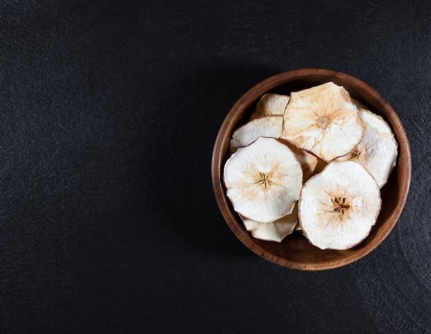 黒い石の背景に木製のボウルに乾燥したリンゴのチップ。