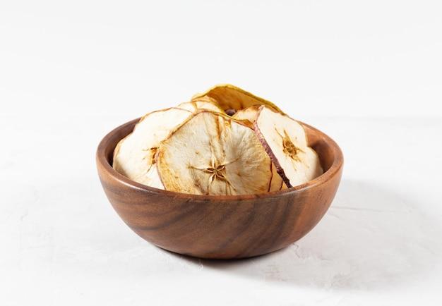 白いコンクリートの背景に木製のボウルに乾燥リンゴチップ。