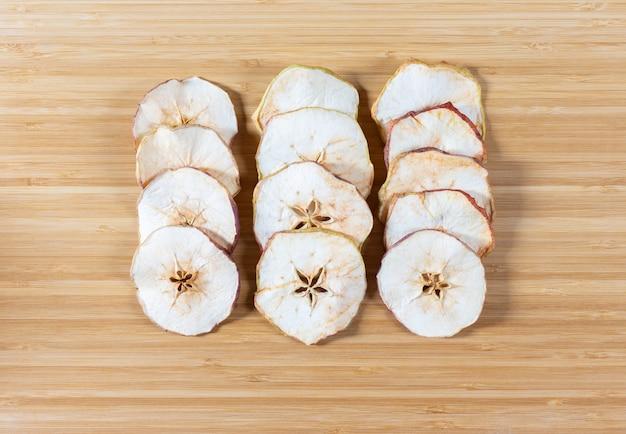 まな板の背景に乾燥したリンゴのチップ。天然有機食品。