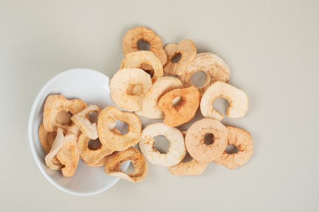 Dried apple chips out of white bowl