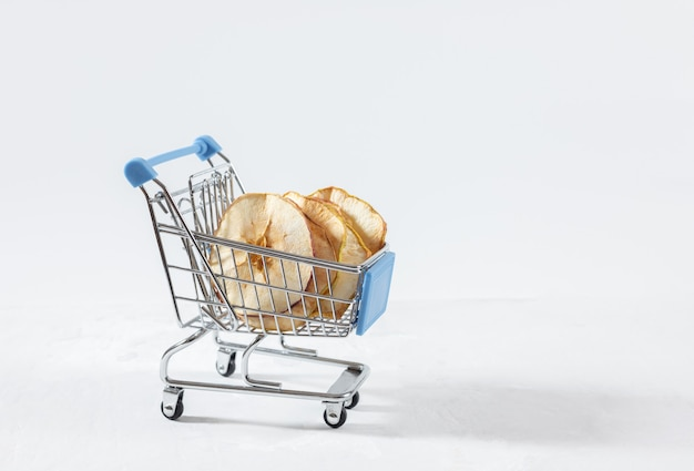 Dried apple chips in a toy grocery cart on a white background.