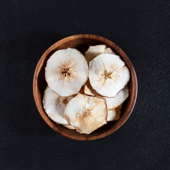 Dried apple chips in a wooden bowl on a black stone background.