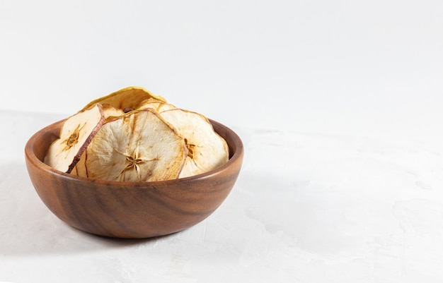Dried apple chips in a wooden bowl on a white concrete background.
