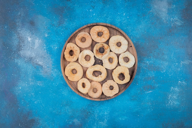 Dried apple chips on wooden plate on blue surface
